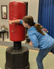 young girl striking heavy bag