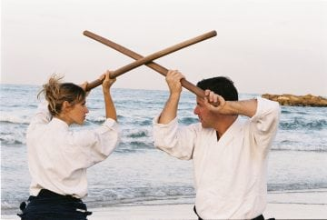 Miles Kessler and student with bokken on beach