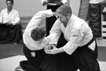 black belt performs aikido shihonage